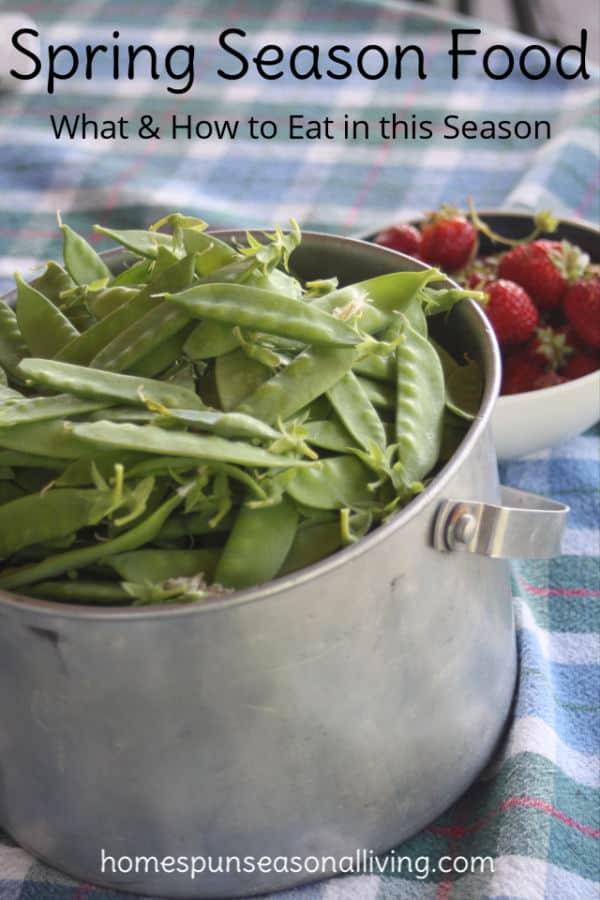 A bucket of snow peas and a bowl of strawberries on a checkered table cloth.