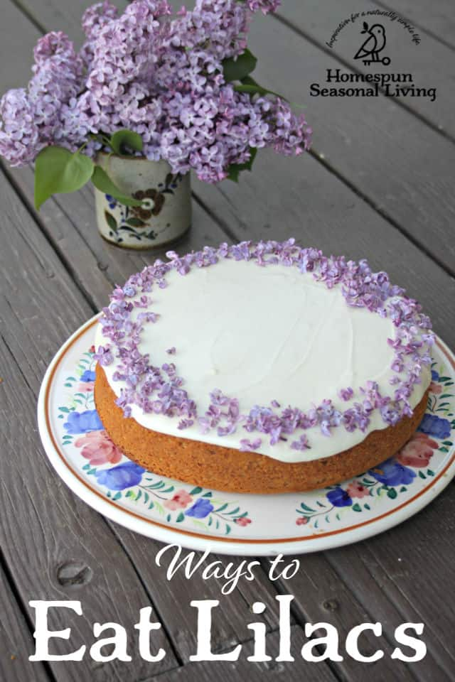 Lilac honey cake on a platter with vase of lilacs in background.