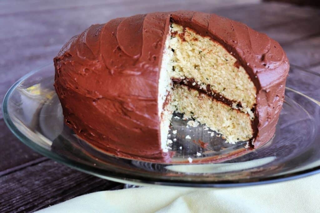 A mint cake with chocolate frosting sitting on a glass cake plate with one slice cut out of the whole.