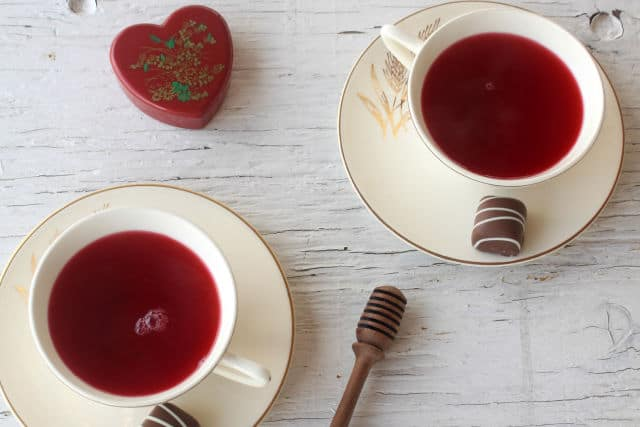 Two cups of hibcus tea in cups on saucers with chocolate candies.