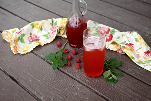 Raspberry lemon balm shrub in a glass with extra pitcher, fresh raspberries, and lemon balm on a table.