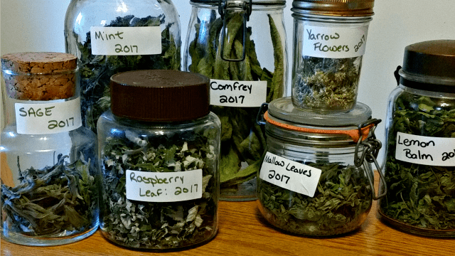 Labeled jars of dried herbs stacked and sitting on a table.