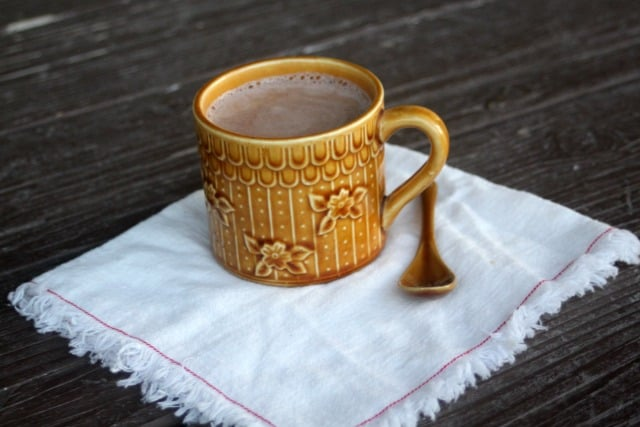 A cup of hot cocoa with a spoon on a cloth napkin.