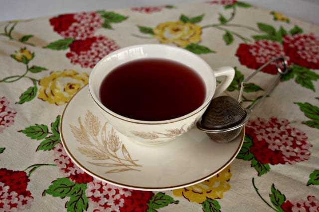 A cup of hibiscus tea in a cup sitting on a saucer with a tea ball on the plate.