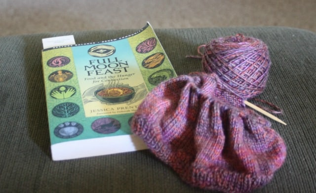 A book and a ball of yarn with hat in progress on knitting needles sitting on a stool.