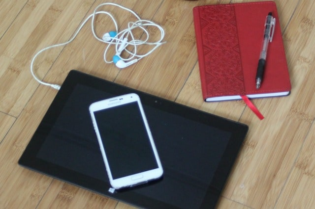 A computer tablet and smart phone with headphones and a journal with pen on a wood table.