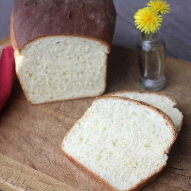 Sliced dandelion bread on cutting board with dandelion flowers in a vase.