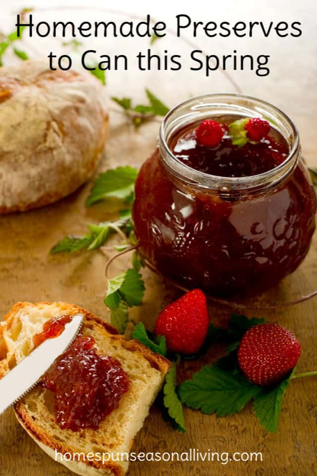 Strawberry jam in an open jar, toast spread with jam and fresh strawberries on a table.