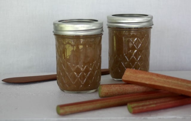 Rhubarb hard cider jam in jars with stalks of fresh rhubarb on a table.