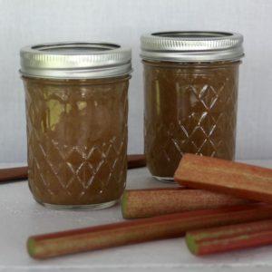 Rhubarb hard cider jam in jars with stalks of fresh rhubarb.