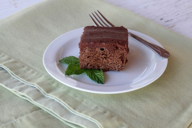 A frosted fresh mint brownie on a plate.