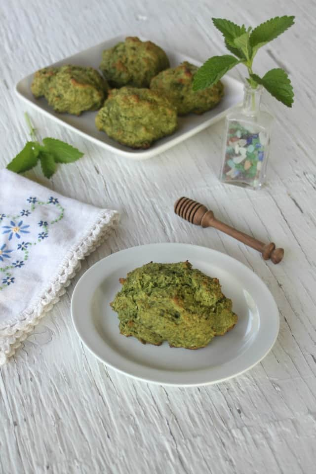 lemon balm drop biscuits on a table with napkin and vase of fresh lemon balm leaves.