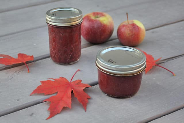 Jars of cranberry apple butter on a table with red maple leaves and fresh apples.