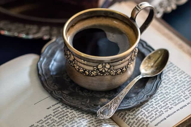 A cup of coffee with teaspoon sitting on a saucer on open book.