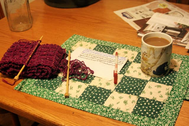 A scarf on knitting needles next to a cup of coffee on table.