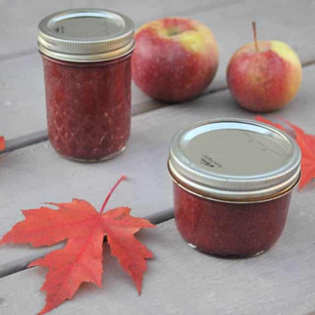 Jars of cranberry apple butter on a table with maple leaves and fresh apples.