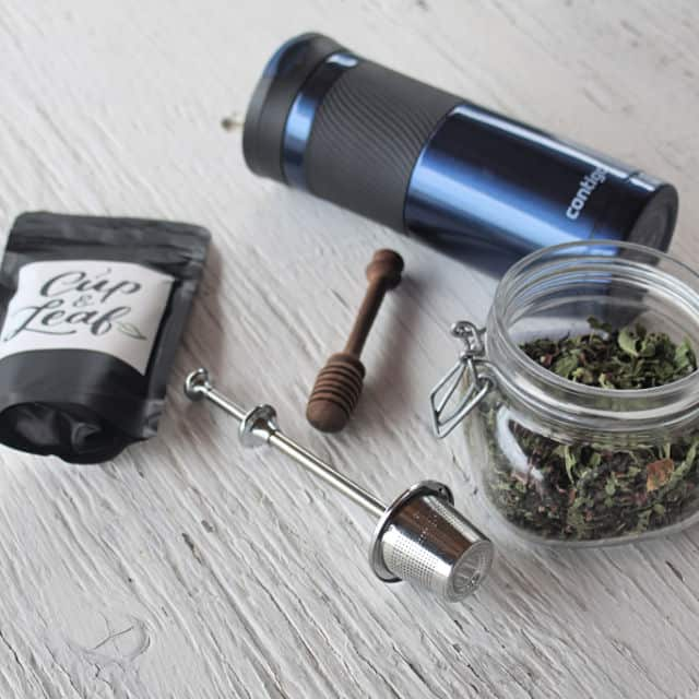 A collection of teas, tea ball, travel mug, and honey dipper for gifts for the tea lover.