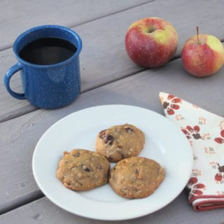 Soft spiced coffee cookies on a plate with cup of coffee, fresh apples, and a cloth napkin.