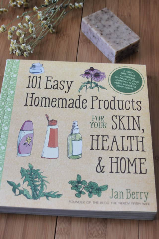 The book 101 Easy Homemade Products on a table with a bar of soap and dried herbs.