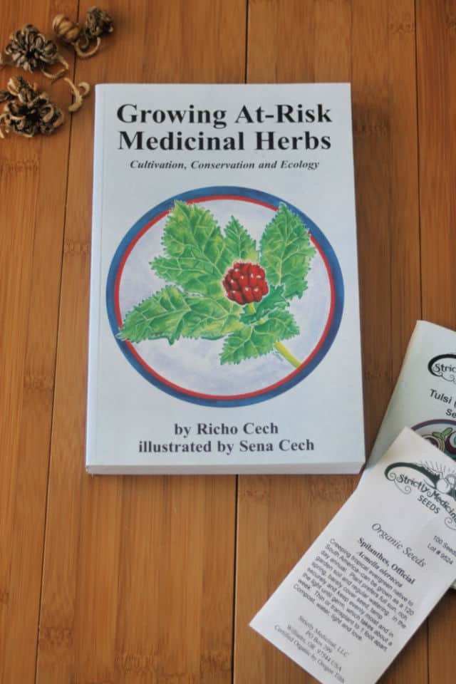 The book Growing At-Risk Medicinal Herbs sitting on a table with seed packets and loose seeds.