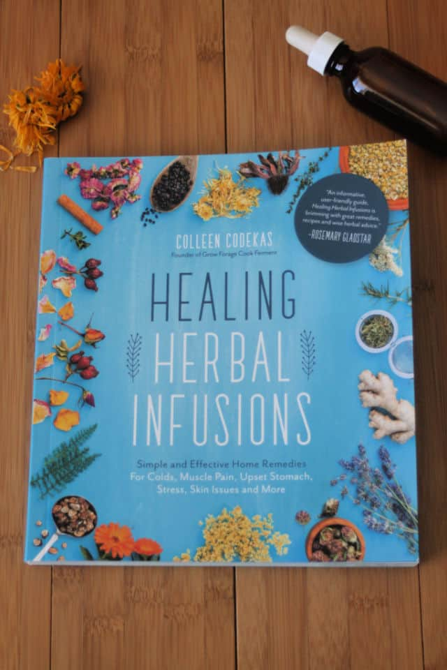 The book Healing Herbal Infusions on a table with dried flowers and tincture bottle.