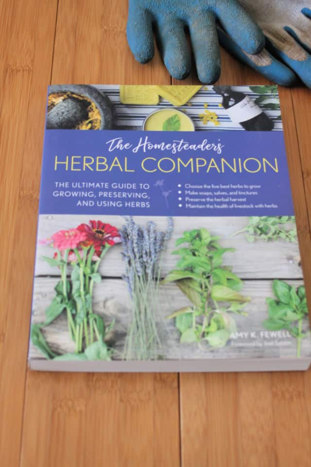 The book The Homesteader's Herbal Companion on a table with a pair of gardening gloves.