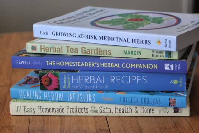 A stack of herbal books on a table.