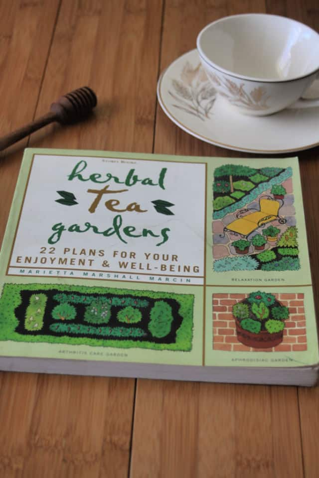 The book Herbal Tea Gardens on a table with honey dipper and tea cup on a saucer.