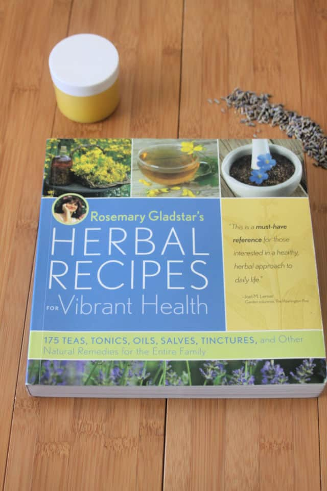The book Herbal Recipes for Vibrant Health on a table with jar of salve and lavender buds.