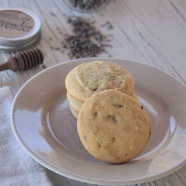 White chocolate lavender cookies on a plate with a napkin, honey dipper, and loose dried lavender buds on a table.