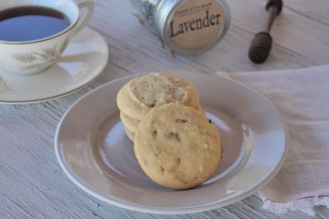 White chocolate lavender cookies on a plate with a napkin, honey dipper, cup of tea, and dried lavender buds in a jar on a table.