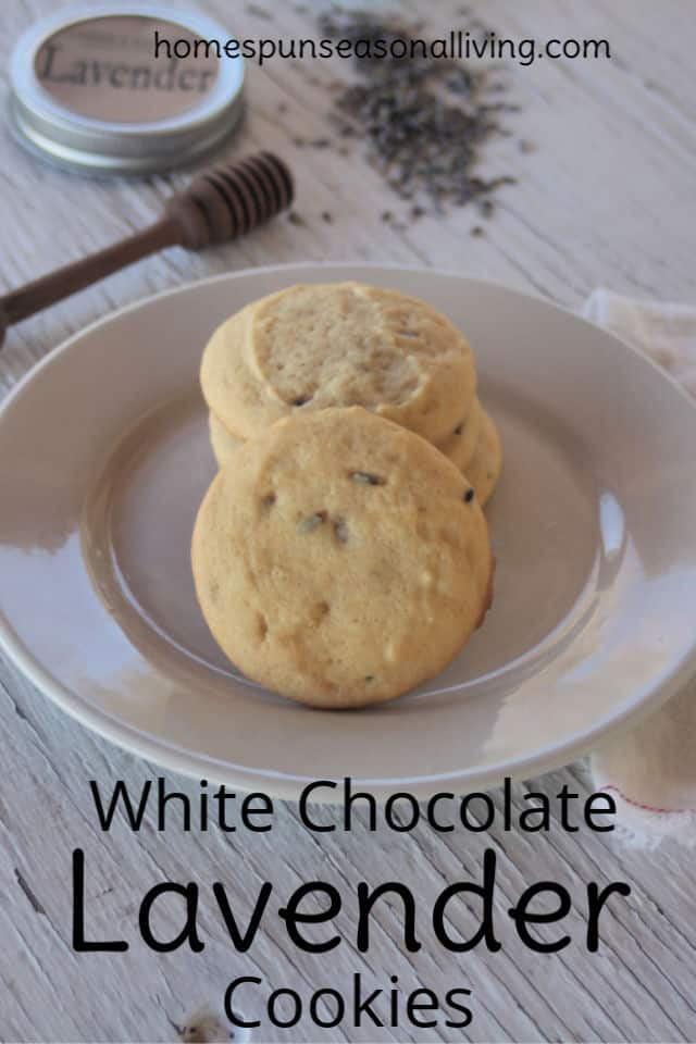 White chocolate lavender cookies on a plate with a napkin, honey dipper, and loose dried lavender buds on a table - with text overlay