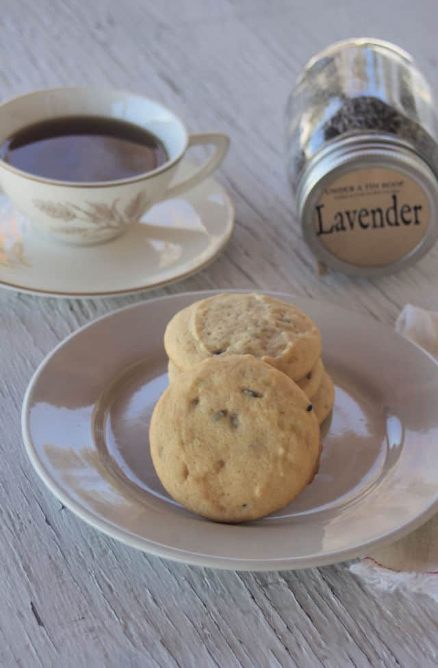 White chocolate lavender cookies on a plate with a napkin, honey dipper, cup of tea, and dried lavender in a jar on a table.