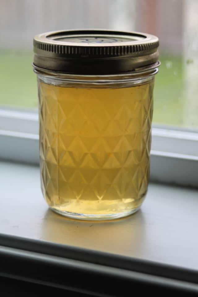 Dandelion jelly in a jar sitting in front of a window.