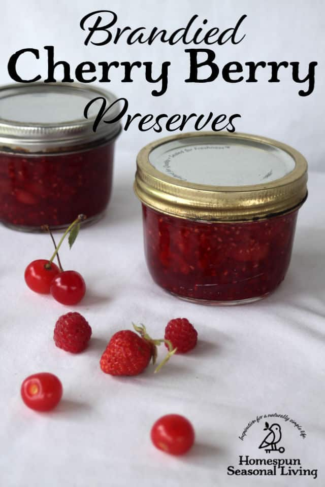 Jars of brandied cherry berry preserves on a table surrounded by fresh cherries and berries.
