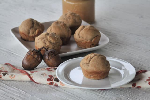 Applesauce muffin on a plate with a napkin and nuts.