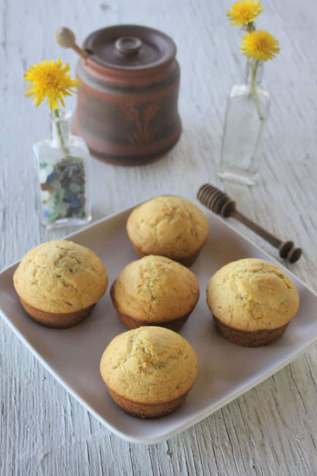 Dandelion muffins on a plate with 2 small bottles full of dandelion flowers behind it.