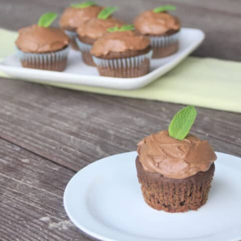 Mint chocolate cupcake on a plate in the foreground with a plate of cupcakes in the background.