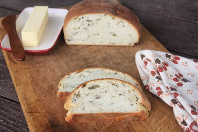 Potato chive bread slices on a cutting board with a napkin and butter in a dish.