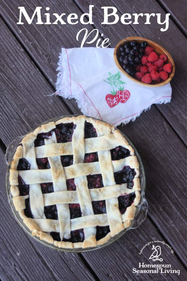 Mixed berry pie with lattice crust seen from above with a napkin and bowl of fresh mixed berries beside it..