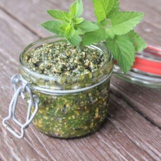 Lemon Balm Oregano pesto in an open jar with fresh herbs in the background.