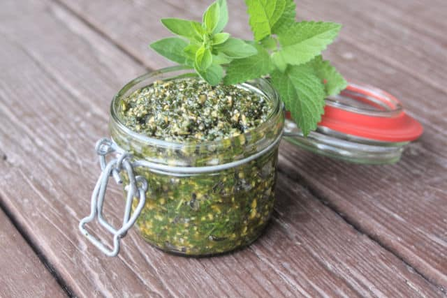 Lemon balm oregano pesto in a glass jar with fresh herbs.