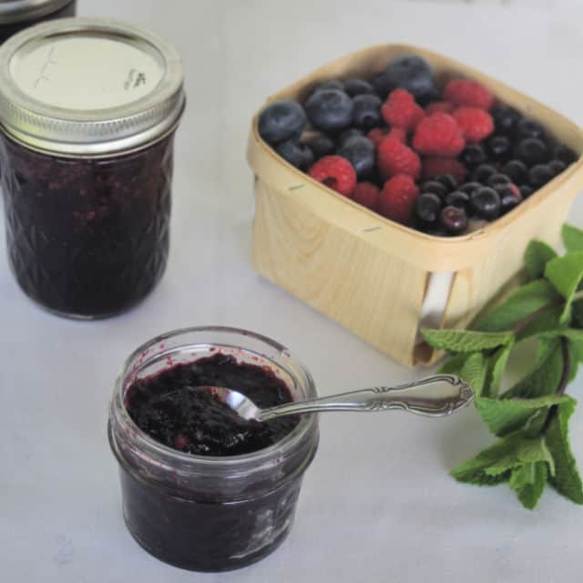 A spoon sticking out of an open jar of minted mixed berry jam.