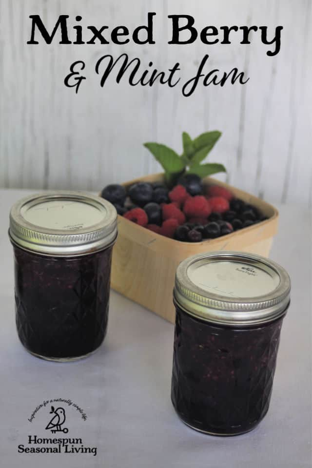 2 jars of minted mixed berry jam sitting in front of a basket of mixed berries.