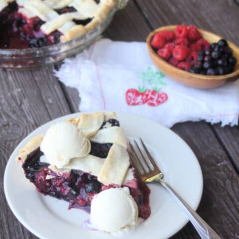 Mixed berry pie slice on a plate with scoops of vanilla ice cream on top.