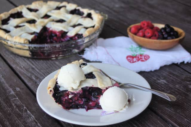 A slice of mixed berry pie on a plate with scoops of vanilla ice cream.
