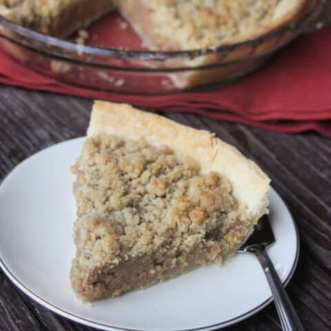 Apple butter pie with crumb topping slice on a plate with a fork.