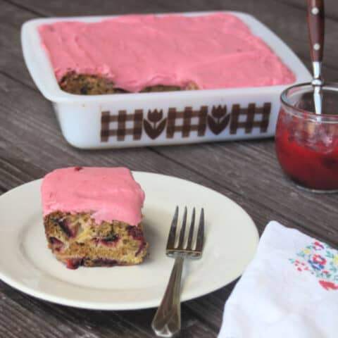 A slice of plum cake with plum jam frosting on a plate with a fork and napkin.