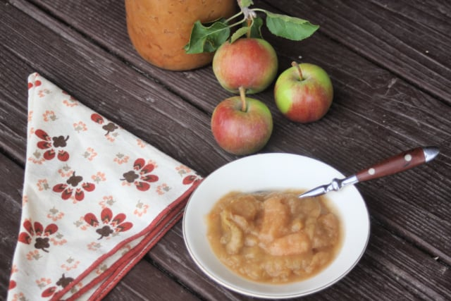 Chunky applesauce in a bowl with a spoon, a napkin to the left and fresh apples behind it.