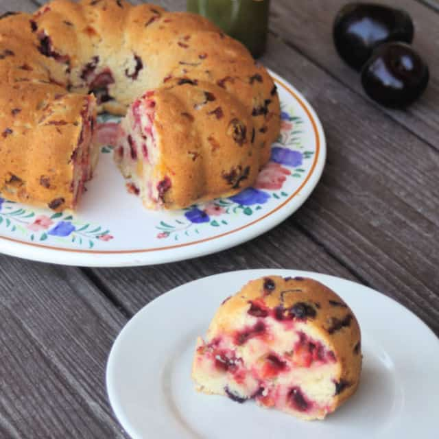 A slice of plum summer cake on a plate with whole bundt cake behind it.